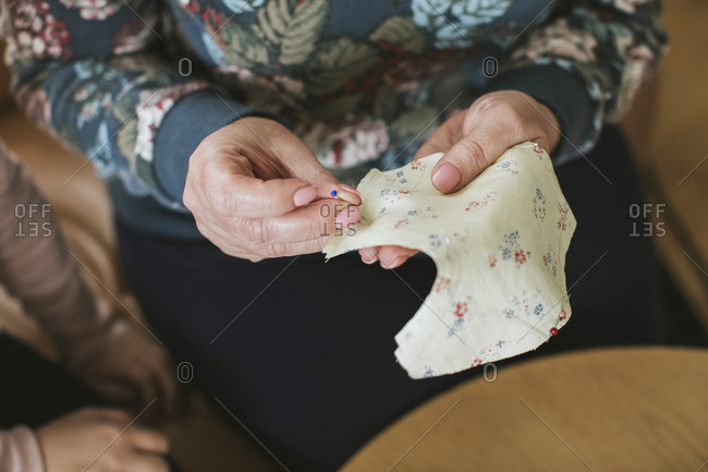 Mature woman holding straight pin and floral textile for sewing face mask at home