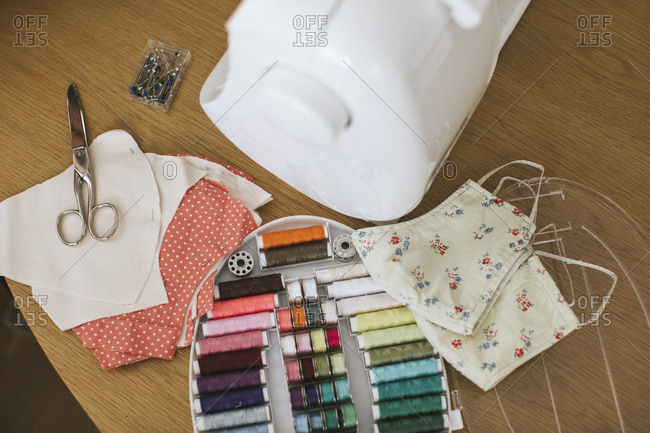 Sewing items with floral protective masks on table at home