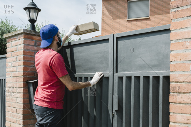 Male delivery person giving package from over gate of house