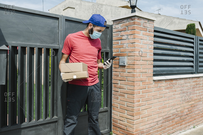 Male postal worker using mobile phone while standing with package against gate