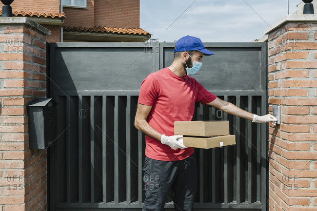 Male delivery person using intercom while standing with package at house gate during coronavirus
