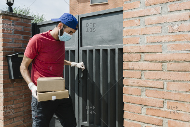 Male postal worker standing by house gate while delivering package during pandemic