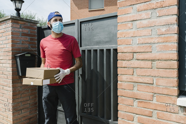 Mid adult male delivery person looking away while holding package and standing against house gate