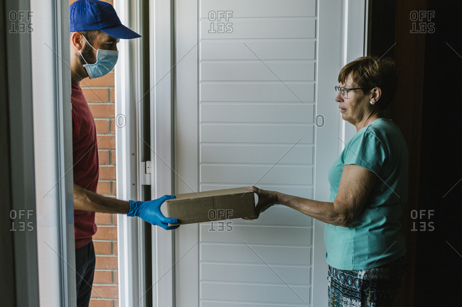 Postal worker delivering package to senior woman at doorway during coronavirus