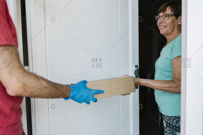 Smiling senior woman receiving package from delivery person at doorway