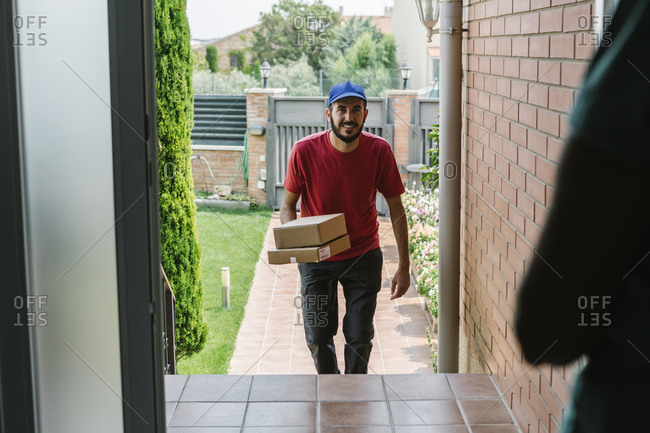 Smiling male postal worker delivering packages to senior woman