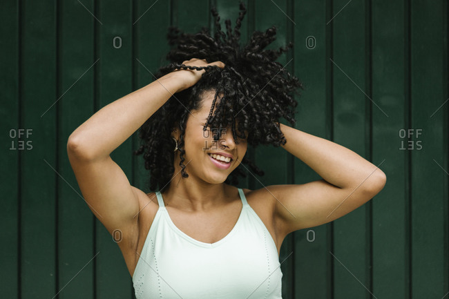 Happy young woman with hand in black curls while standing against green metal door