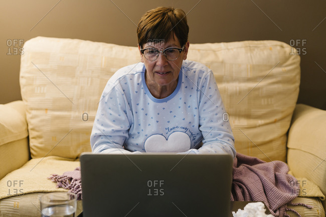 Retired senior woman discussing illness with doctor over video call through laptop at home