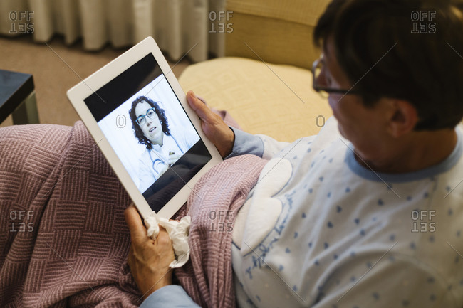 Doctor discussing illness with senior woman through video call