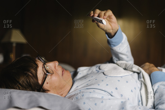Elderly woman looking at thermometer while lying on bed at home