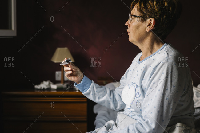Ill senior woman looking at thermometer while sitting on bed at home