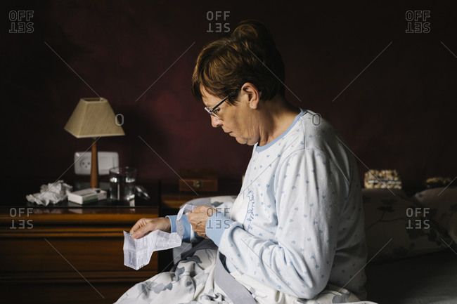 Ill senior woman reading instructions of prescription medicine while sitting on bed at home