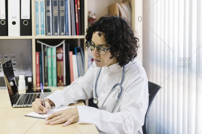 Female doctor writing by laptop while sitting at desk in office