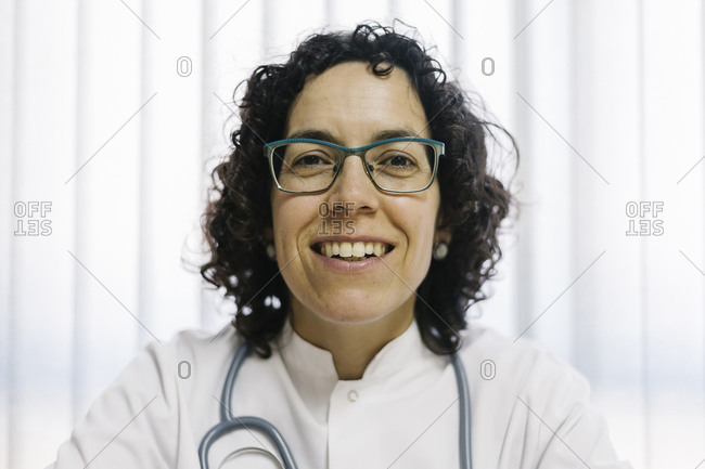 Smiling mature female doctor at medical clinic