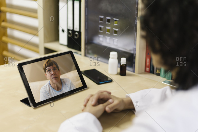 Senior woman on digital tablet screen during video call with doctor