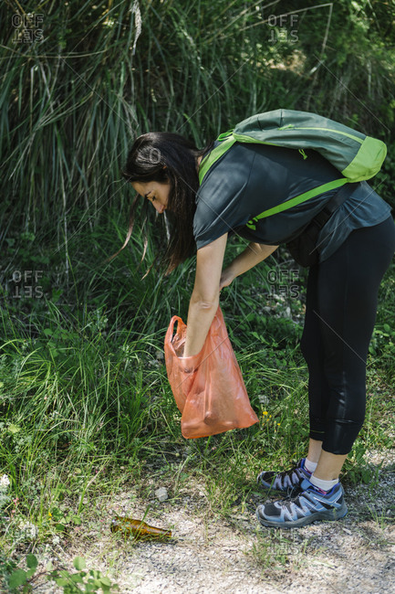 Hiker picking up trash in the woods