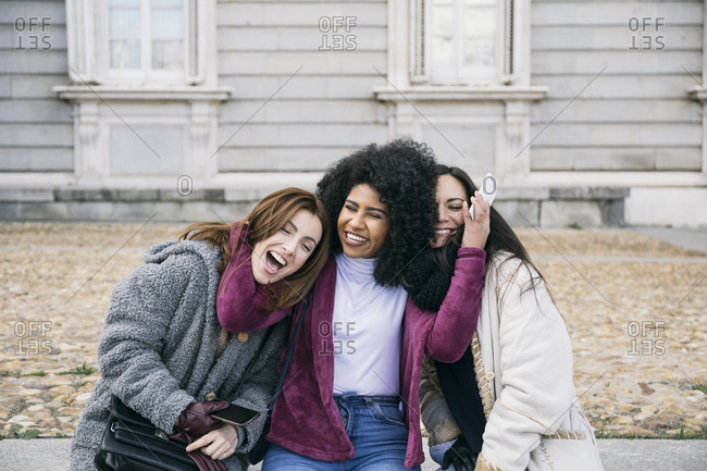 Happy young woman embracing female friends while sitting against Madrid Royal Palace- Spain
