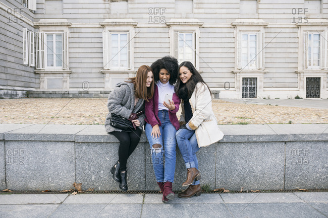 Female friends using smart phone while sitting on retaining wall against Madrid Royal Palace- Spain