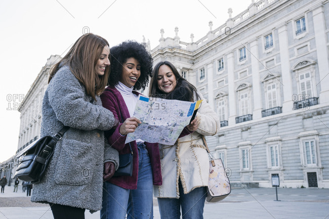 Female tourists analyzing map while standing against Madrid Royal Palace- Spain