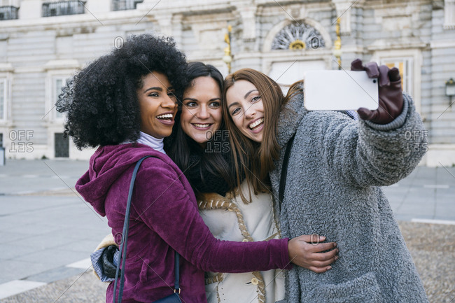 Happy female friends taking selfie with smart phone while standing against Madrid Royal Palace- Spain