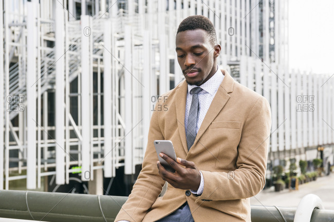 Young businessman using smartphone in the city