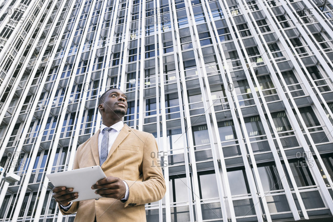Young businessman in front of modern office building in the city holding a tablet