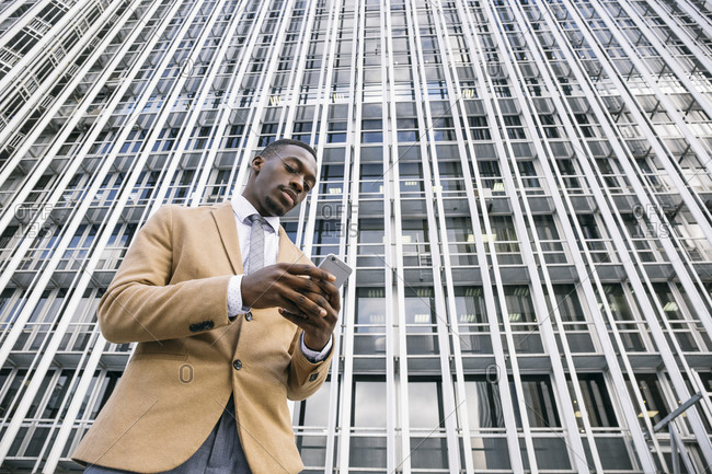 Young businessman in front of modern office building in the city using smartphone