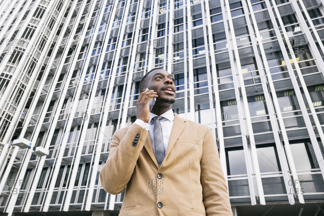 Young businessman in front of modern office building in the city on the phone