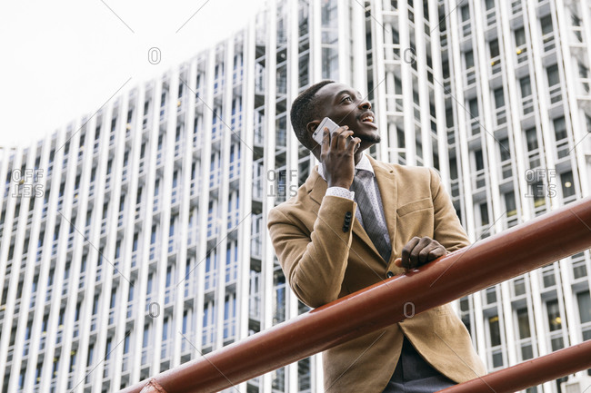 Young businessman leaning on a railing in the city talking on the phone