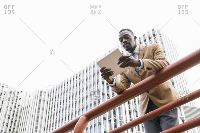 Young businessman leaning on a railing in the city using a tablet
