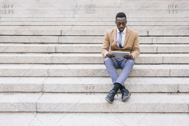 Young businessman sitting on stairs using a tablet