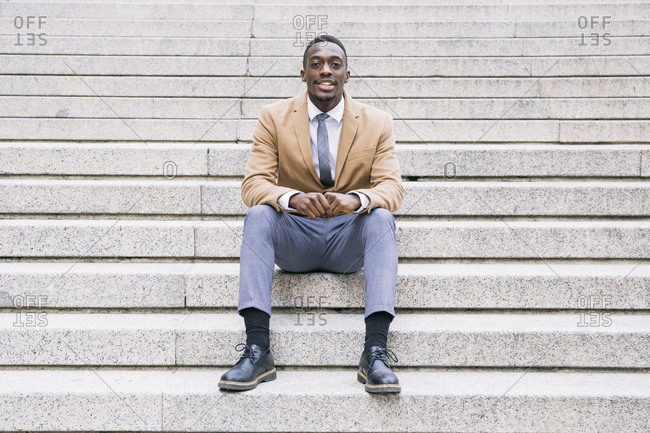 Portrait of confident young businessman sitting on stairs
