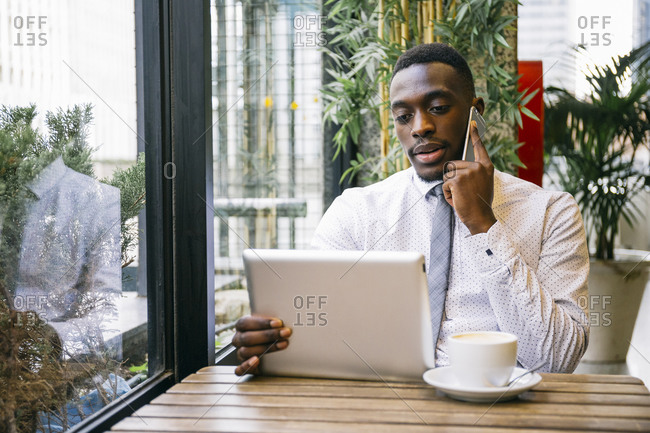 Young businessman using tablet and smartphone in a cafe