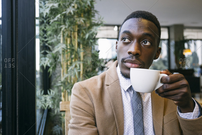 Portrait of young businessman drinking a cup of coffee in a cafe