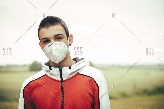 Portrait of teenager wearing protective mask outdoors