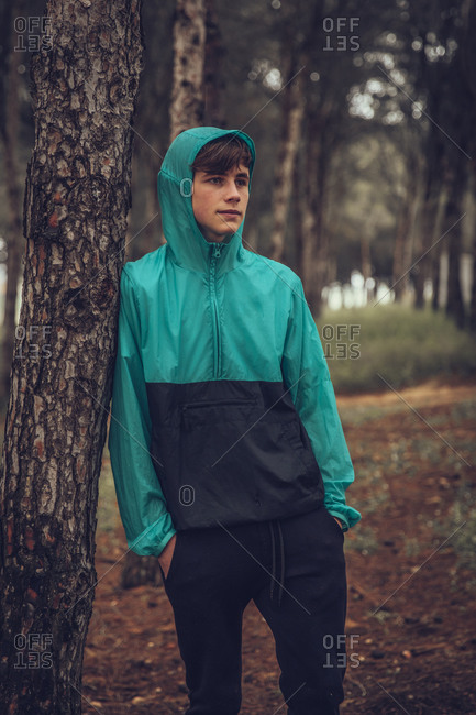 Teenager wearing raincoat and leaning on tree