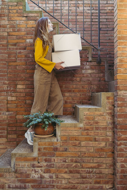 Young woman with white boxes moving up on steps by brick wall