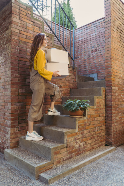 Young woman carrying white boxes while moving up on steps by brick wall