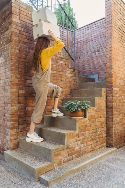 Young woman carrying boxes on head while walking over steps by brick wall