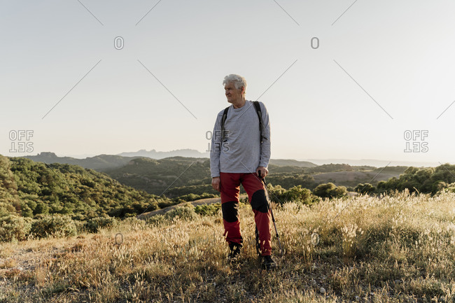 Senior male hiker looking away while standing with hiking pole on plants against clear sky
