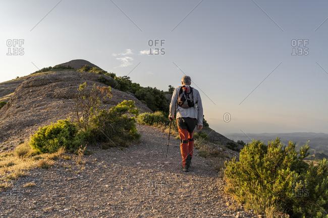 Active senior man walking with hiking pole on mountain during sunset