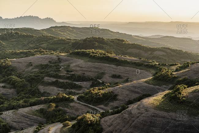 Scenic view of landscape with winding road against sky during sunset