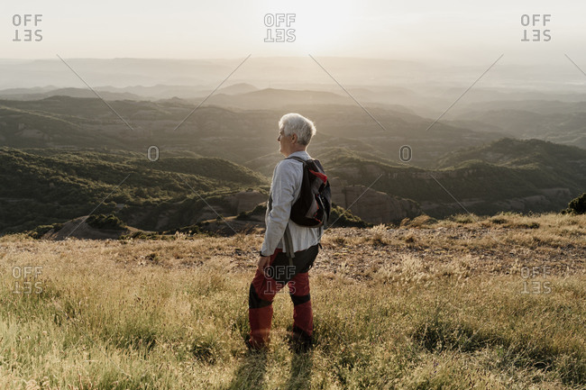 Active senior man standing on mountain while looking at landscape during sunset
