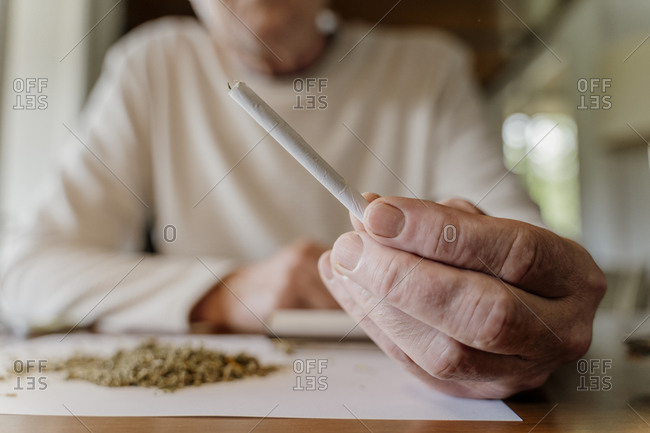 Close-up of senior man holding marijuana joint at home