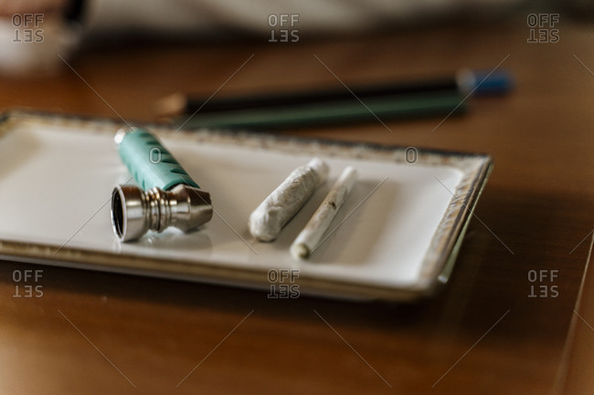 Close-up of marijuana joints and pipe in tray on table