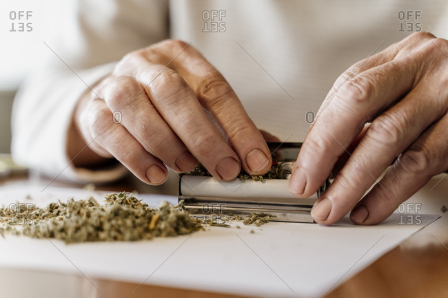 Midsection of retired senior man rolling weed on table