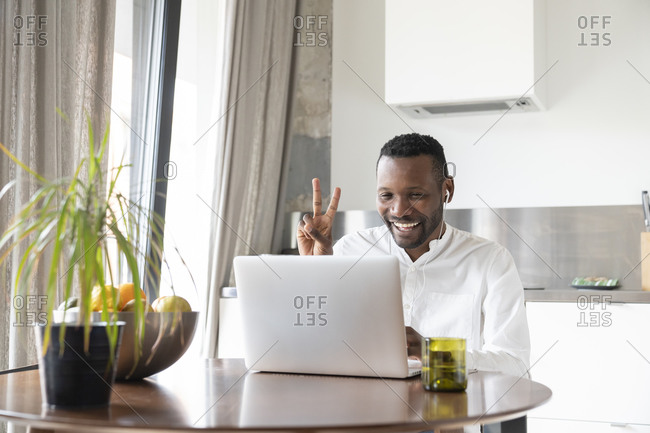 Portrait of happy man sitting at kitchen table during video chat showing victory sign