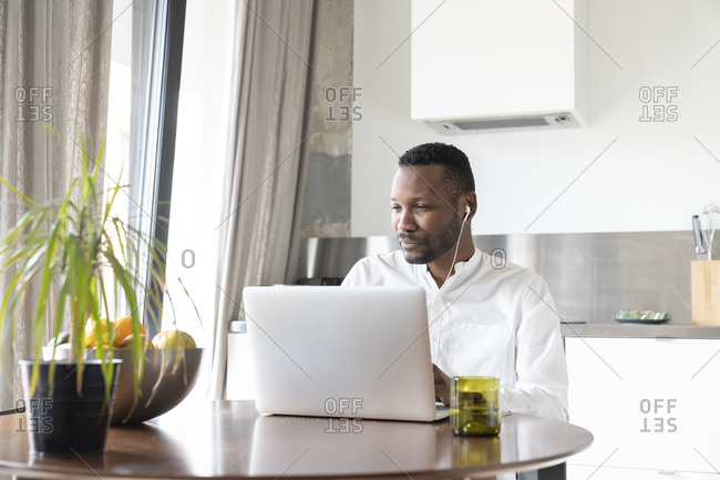 Portrait of man using laptop and earphones at home