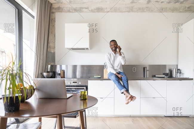 Portrait of smiling man on the phone sitting on kitchen counter in modern apartment