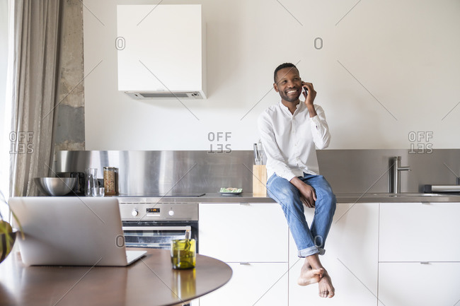 Portrait of smiling man on the phone sitting on kitchen counter at home